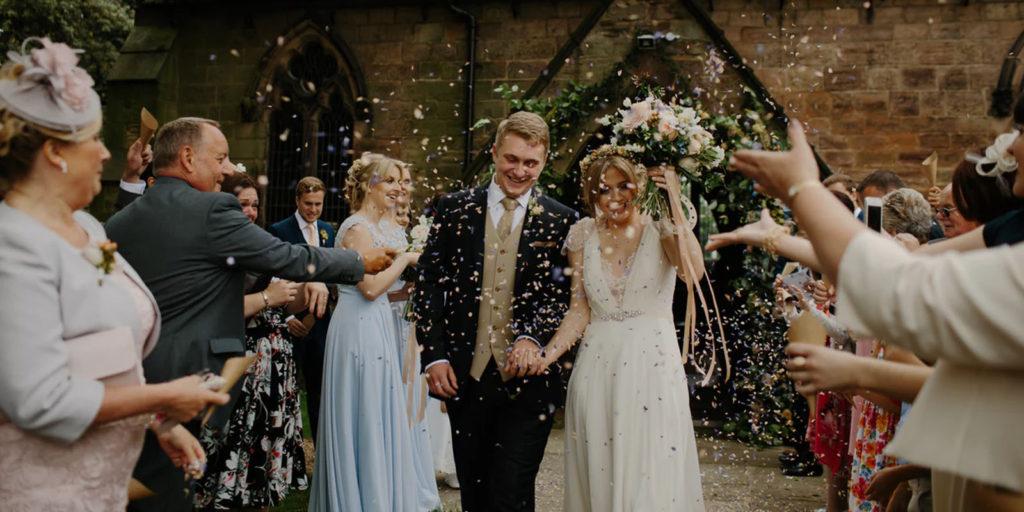 throwing confetti as bride & groom walk through wedding party