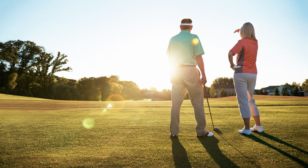 a man and woman at a golf course looking towards the sun