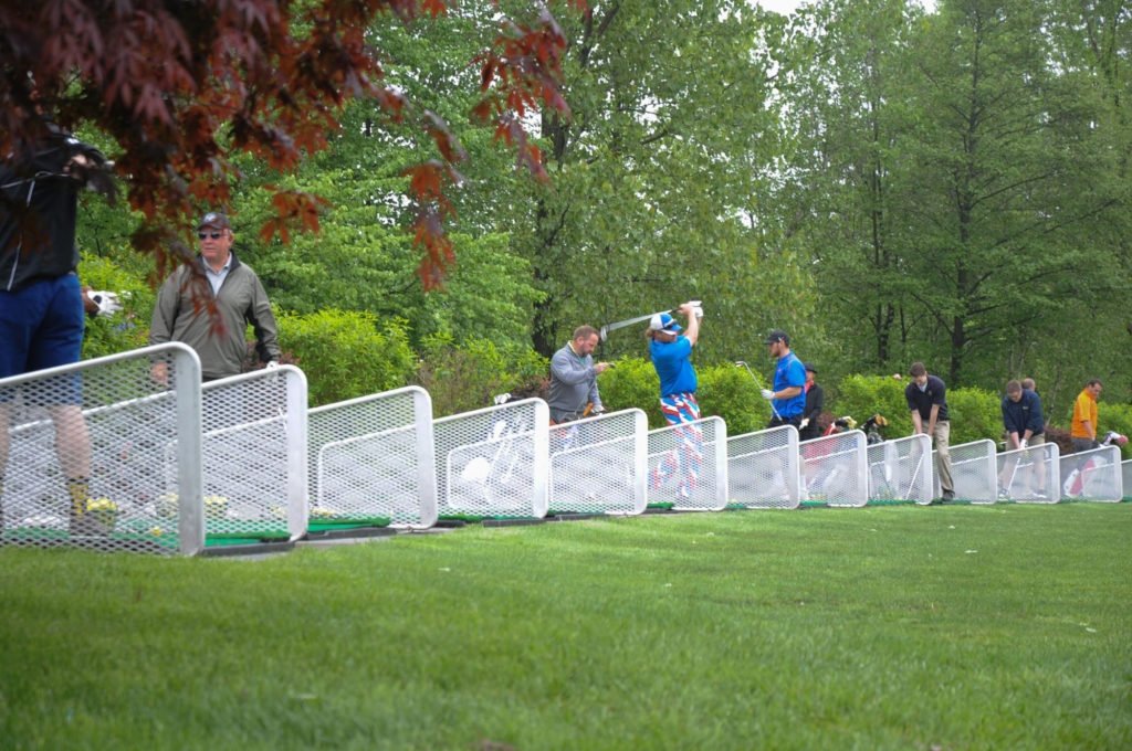 Multiple golfers warming up at the Apple Greens Golf Course driving range