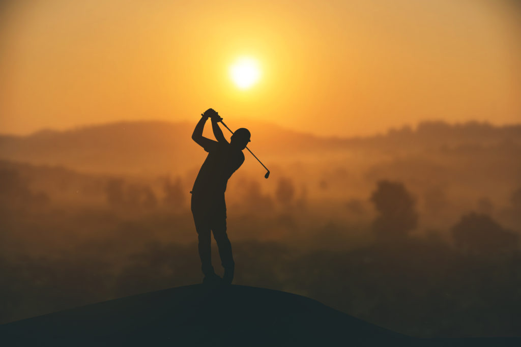 silhouette of a man golfing off a mountain