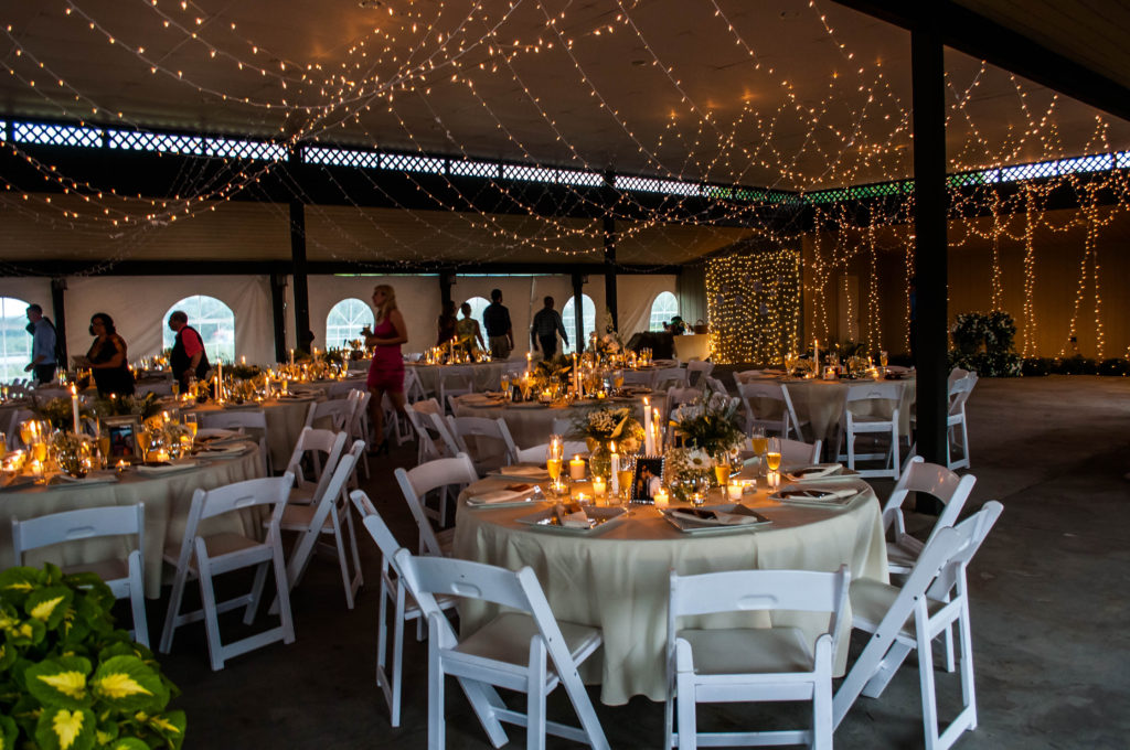 A covered patio with assorted chairs and table settings for a wedding