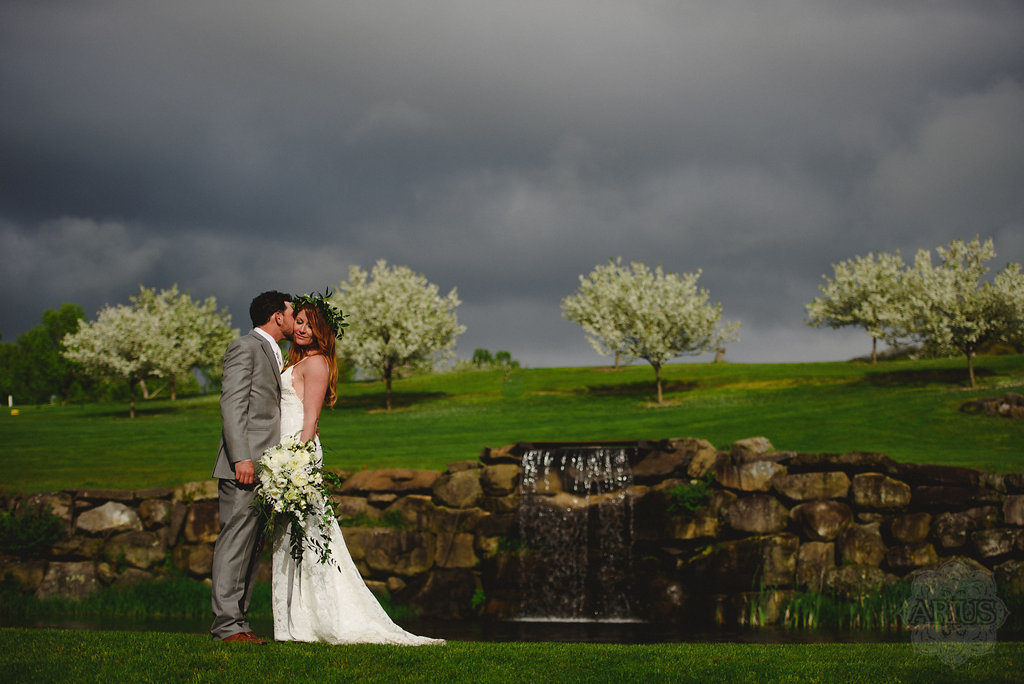 A bride and groom escape their wedding party for a quick wedding photo on Apple Greens Golf Course