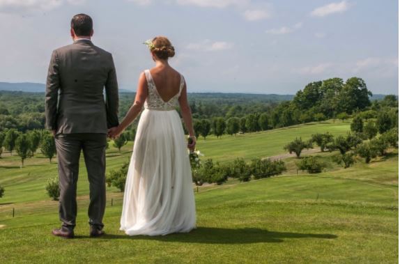 bride and groom holding hands overlooking apple greens golfcourse