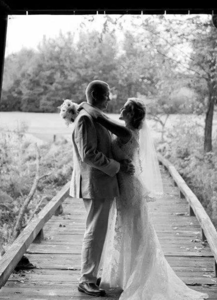 black & white bride & groom hugging on wood walkway